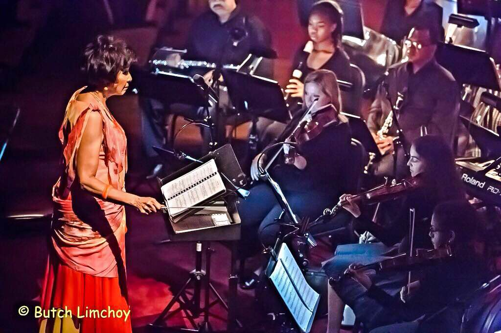 Gretta conducts the LES MIS orchestra including,  American Kathleen Foster (viola), American Gail Hernández Rosa (1st violin), and Trinidadian Amanda Manmohan (violin).